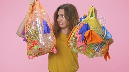 consumo : Displeased young woman is holding string bags with plastic waste screaming to the camera isolated over pink background