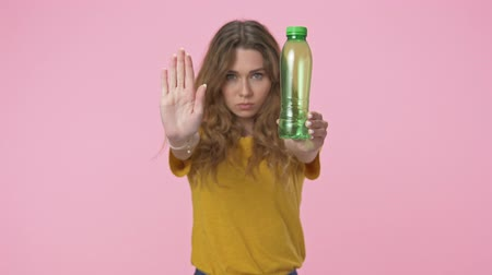 ninhada : A nice young woman shows a stop gesture while holding a plastic bottle isolated over pink background Vídeos