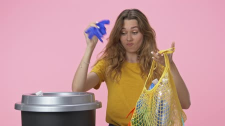 consumo : A good-looking young woman starts to sort garbage then puts her string bag to the litter isolated over pink background