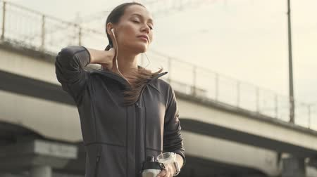 закрытыми глазами : Mystery pretty asian sports woman in earphones touching her neck with closed eyes while holding bottle with water outdoors Стоковые видеозаписи