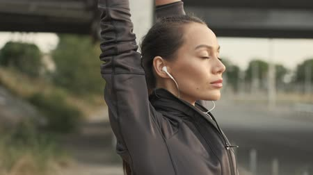 закрытыми глазами : Close up view of calm pretty asian sports woman in earphones stretching with arms outdoors Стоковые видеозаписи