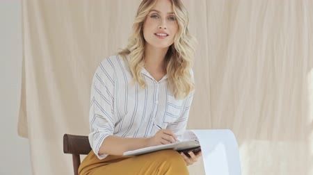 camiseta : A beautiful young woman is writing something in her clipboard while smiles and looks to the camera isolated over fabric background Stock Footage