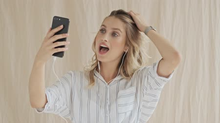 hóquei : A beautiful woman with blond hair is having a video call on her cellphone with wired headphones isolated over fabric background