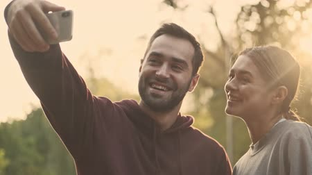 selfie girl : Cheerful young pretty couple making selfie on smartphone in park outdoors