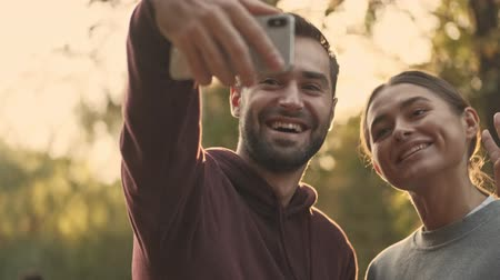 férfias : Close up view of Joyful young pretty couple making selfie on smartphone in park outdoors