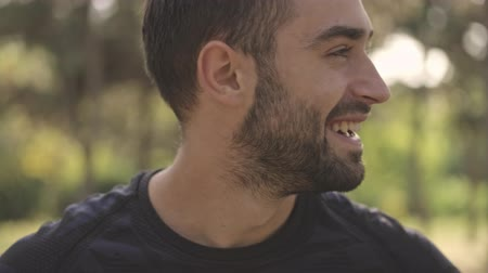 barbu : Close up view of Joyful handsome sportsman looking around in park outdoors