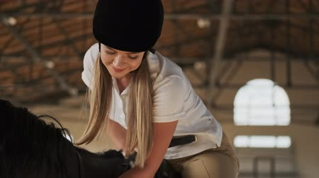 stabilní : Beautiful blonde girl is petting a horse while riding it in the covered stable