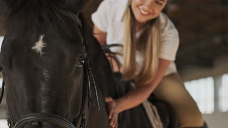 stabilní : Close up view of a smiling girl is petting a horse while riding it in the covered stable