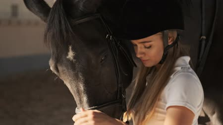stabilní : Nice girl is petting a head of brown horse while standing near it in the covered stable