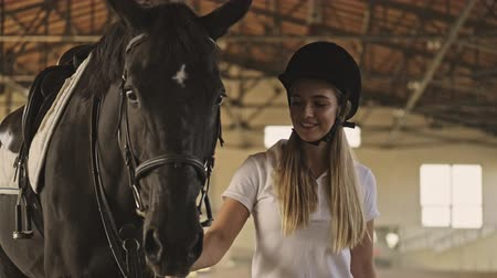 stabilní : A teenage girl jockey is walking with a horse in the covered stable