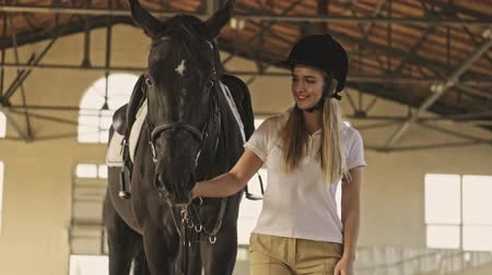 stabilní : A teenage girl jockey wearing riding clothes is going to rise a horse in the covered stable