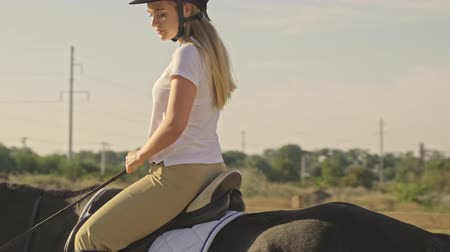 rural area : Side view of a teenage girl jockey is riding a brown horse at the horse yard Stock Footage