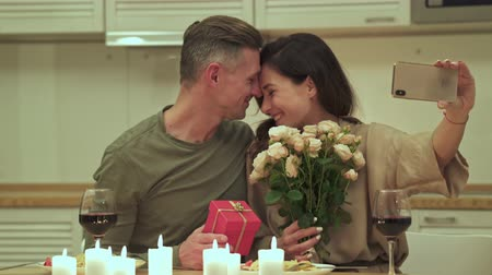 amado : Happy couple taking selfie while looking at each other with flowers and gift in a romantic setting at home Stock Footage