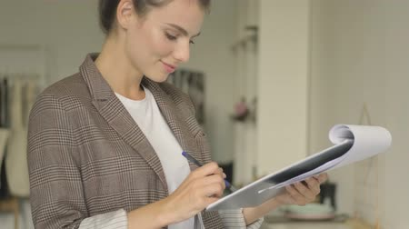 подпись : An attractive stylish young businesswoman is checking the documents and putting a signature in the white office indoors