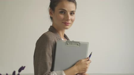 kafeterya : A pretty young woman is holding a folder of documents while looking to the camera indoors
