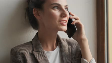 maravilhoso : Wonderful young woman is talking on the phone while sitting near the window Stock Footage