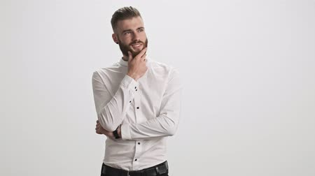 ひげを剃っていない : A stylish bearded man is touching his chin while thinking about something isolated over white wall background 動画素材