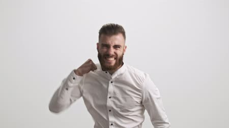 ひげを剃っていない : A happy smiling bearded man is showing a winner gesture isolated over white wall background