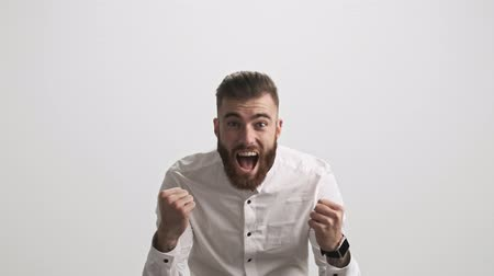 broda : A happy screaming bearded man is showing a winner gesture with both hands isolated over white wall background