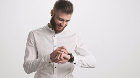 finom : A smiling young bearded man is using his smart watch isolated over white wall background
