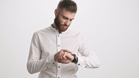небритый : A calm serious young bearded man is using his smart watch isolated over white wall background