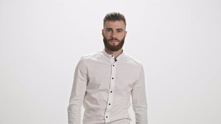 borotválatlan : A handsome young bearded man wearing a white shirt is walking to the camera isolated over white wall background Stock mozgókép