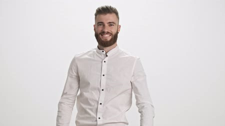 focalizada : A positive smiling young bearded man wearing a white shirt is walking to the camera then touching his hair isolated over white wall background