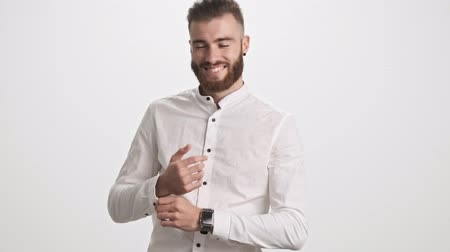 ひげを剃っていない : A positive smiling young bearded man wearing a white shirt is walking to the camera while correcting his cufflinks isolated over white wall background 動画素材
