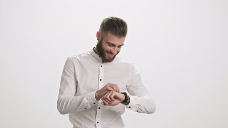 borotválatlan : A stylish smiling young bearded man wearing a white shirt is walking to the camera while using his smart watch isolated over white wall background Stock mozgókép