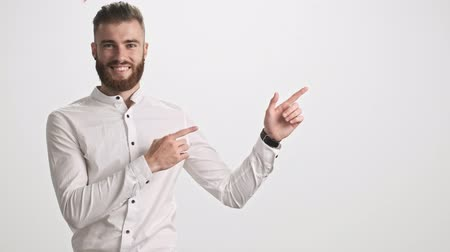 both : A positive young bearded man wearing a white shirt is pointing to the side with both hands isolated over white wall background Stock Footage