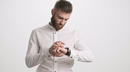 finom : A handsome serious bearded man is using his smart watch or fitness tracker isolated over white wall background