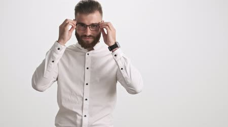 ひげを剃っていない : A positive young bearded man wearing a white shirt puts on glasses isolated over white wall background