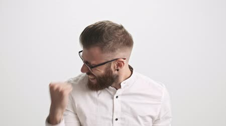 ひげを剃っていない : An attractive happy young bearded man wearing white shirt is doing a winner gesture isolated over white wall background 動画素材