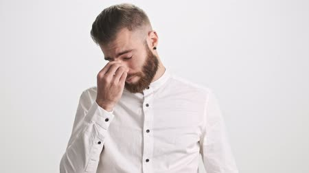 undo : A tired young bearded man takes off his glasses and touches his bridge of nose and undo the top button of his shirt isolated over white wall background