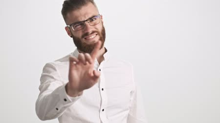 брюнет : A young bearded man wearing white shirt and glasses is gesturing negatively with his finger raised isolated over white wall background Стоковые видеозаписи
