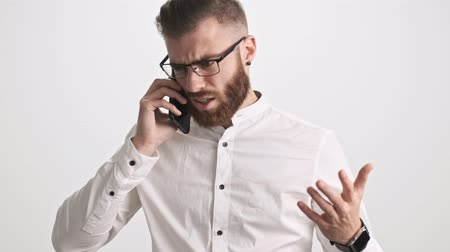 puzzled : A young bearded man wearing white shirt and glasses is having argue during phone call isolated over white wall background Stock Footage