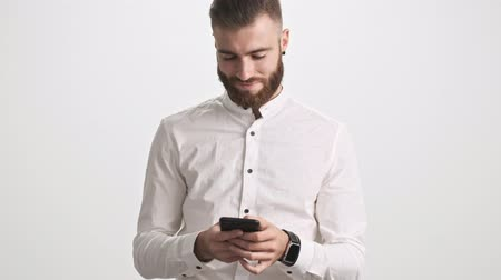 barbu : A positive calm young bearded man wearing white shirt is using a smartphone isolated over white wall background Vidéos Libres De Droits