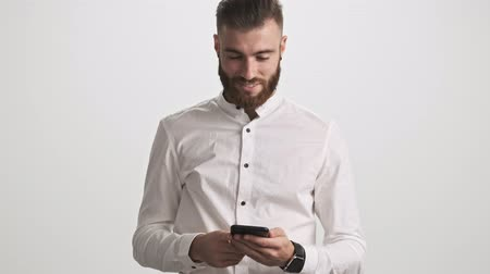hóquei : A calm focused young bearded man wearing white shirt is using his phone then looks to the camera and does a hello gesture isolated over white wall background Stock Footage