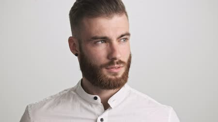 emelt : A calm bearded man wearing white shirt is opening his eyes to the camera isolated over white wall background