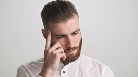 broda : A thinking bearded man wearing white shirt is touching his chin while coming up with the idea about something isolated over white wall background Wideo