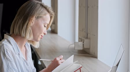escritor : A concentrated nice blonde woman is writing something on her notebook while working on a laptop in the office near the window Stock Footage