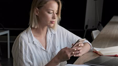 escritor : A serious focused young blonde woman typing on her smartphone while sitting near the window indoors Stock Footage