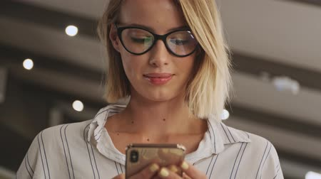 lecture : A close-up view of a smiling woman wearing eyeglasses is using a phone while sitting in a conference hall