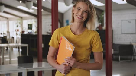 положительный : A smiling beautiful woman is holding a folders with files while standing in a conference hall Стоковые видеозаписи