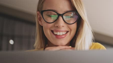 lecture : A close-up view of a pretty smiling woman wearing eyeglasses is working on her laptop while sitting at the desk in a conference hall