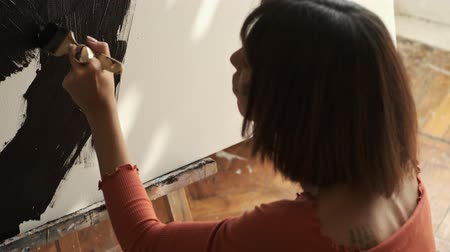 guache : Back view of the attractive caucasian young woman in brown t-shirt drawing with a brush on an easel Stock Footage