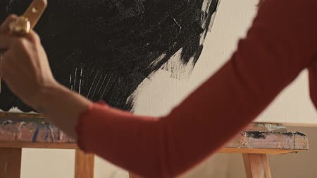 guache : Cropped view of the attractive caucasian young woman in brown t-shirt drawing a picture with a brush on an easel Stock Footage
