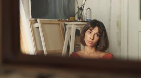 guache : Attractive caucasian young woman painter in a brown t-shirt thinking about something and looking around