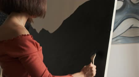 guache : Side view of pensive caucasian young woman in a brown t-shirt drawing on an easel Stock Footage