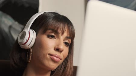 палитра : Beautiful caucasian young woman with headphones working on a laptop